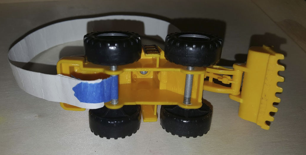 Bottom of a plastic toy digger showing tape around the axle.